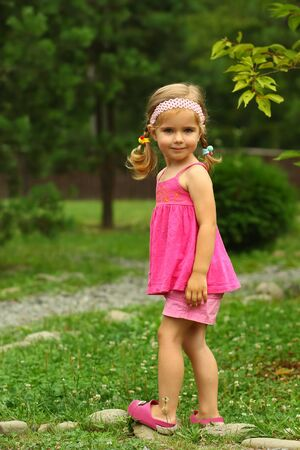 Portrait of a cute two year old toddler girl in pink, balancing on rocks in the park