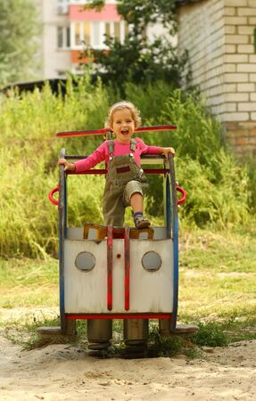 Happy shouting emotional toddler girl pilot posing on playground helicopter
