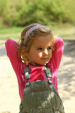 Cute sunlit toddler girl in pink posing hands behind head outdoor