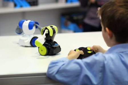 Boy playing battle fighting robots with remote control. Robotics, STEM