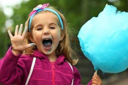 Closeup portrait of happy toddler girl eating bright blue cotton candy
