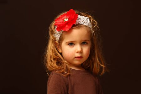 Portrait of cute two year old toddler with a red flower headband, isolated on black