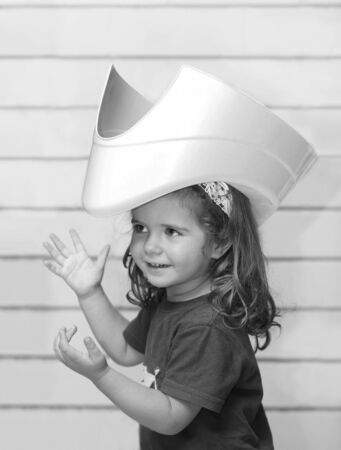 Black and white candid portrait of a funny toddler girl with a potty on her head