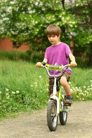 Sechs Jahre alter Junge mit dem Fahrrad im Löwenzahnfeld