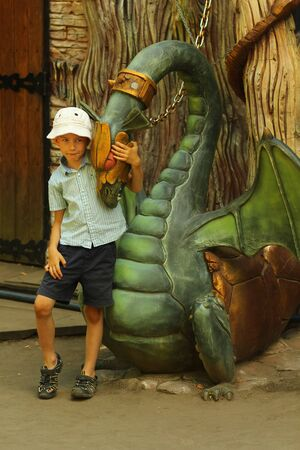 Boy and a statue of a mythical chained dragon
