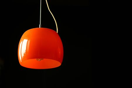 Black background with a warm orange hanging lamp and negative space Stockfoto - 149229352