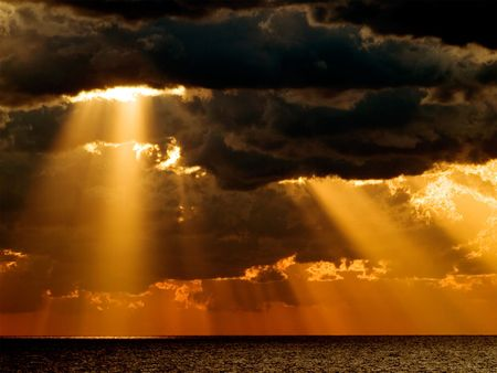 Sunrise over sea with dark dramatic clouds. Stock Photo