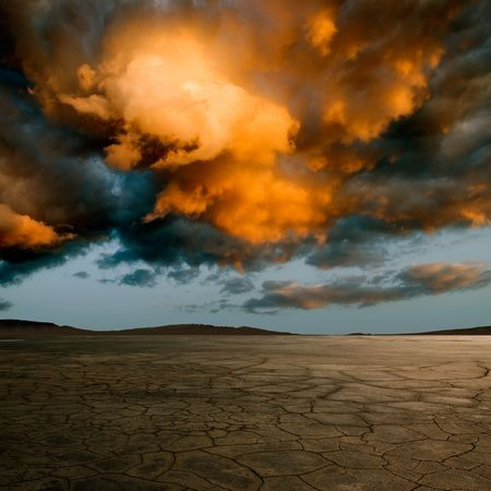 Desert with cracked ground and dramatic clouds. photo