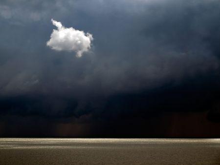 verdunkeln: Wei�e solit�re kleinen Wolke auf dunkle Himmel Hintergrund. Lizenzfreie Bilder
