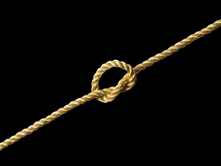 Knot on golden rope on black background (isolated).