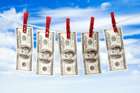 Dollars on a rope isolated on blue sky background. photo