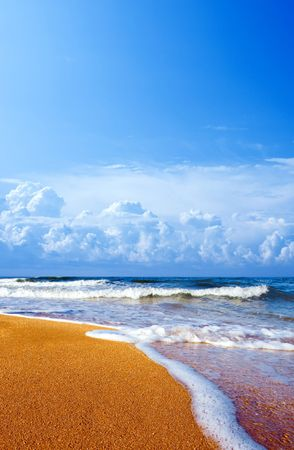 Sandy shore and white clouds on blue sky background. photo