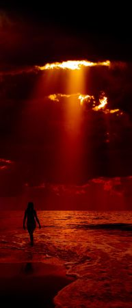 Silhouette of girl and dramatic dark red sky with sunbeam on background. photo