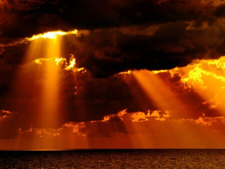 dramatic: Dark clouds with sun rays over sea.