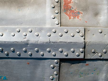 untidily: Abstract worn riveted aluminic surface with patch.