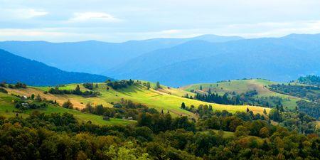 Ukrainian tranquil autumnal landscape with meadow and mountains. Banco de Imagens