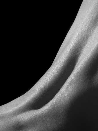 desnudo artistico: Mujer atr�s aislada sobre fondo negro.