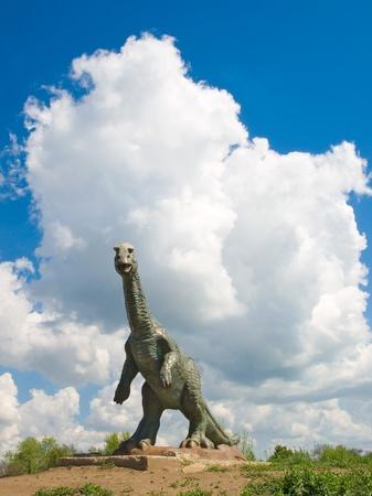 Bronze statue of dinosaur on sky background. photo