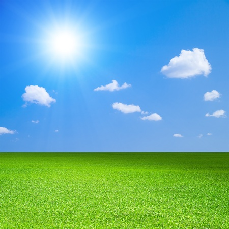 field and sky: Green field, blue sky with white cloud and bright sun. Stock Photo