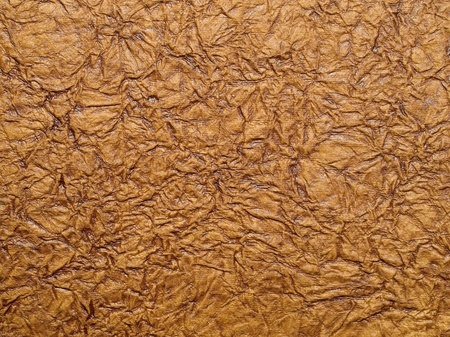 Wrinkled brown paper closeup texture background. photo