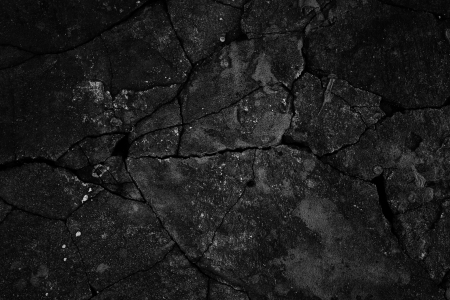 Black cracked concrete texture closeup background.