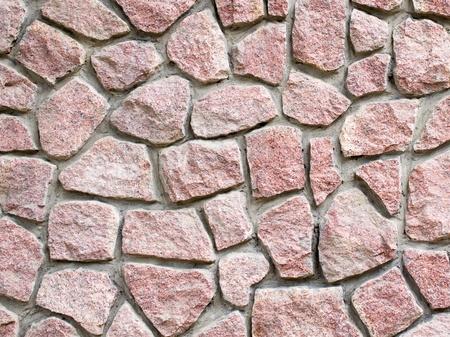 rubble: Red granite masonry wall closeup background.