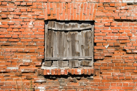 Blocked window on the red brick wall background  photo