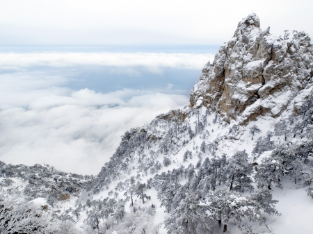 steep cliff: Mountain over clouds - wintry landscape.