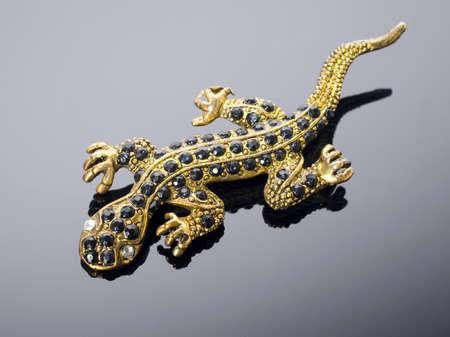 Golden lizard  brooch  on grey background  photo
