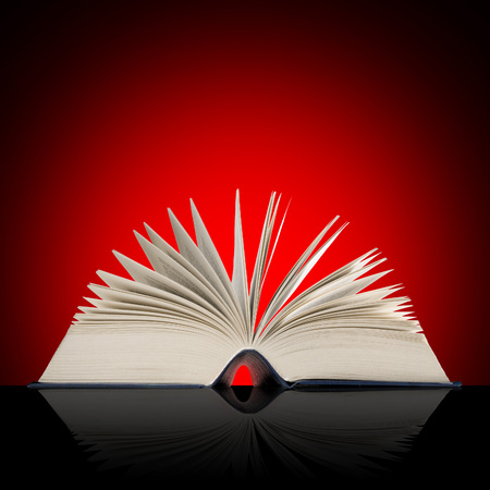 Big open book on red shaded background.
