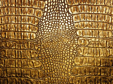 Golden crocodile leather closeup background. Imagens
