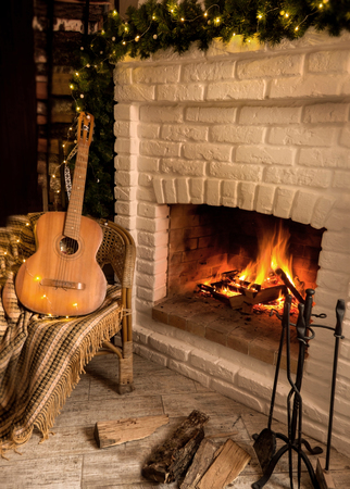 Burning Fireplace Decorated With Christmas Garland Near The