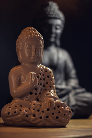 Two Buddha statuettes on a wooden table Stock Photo
