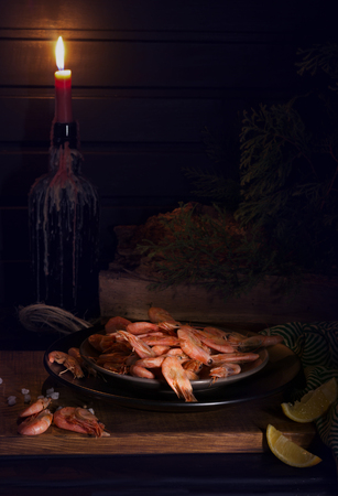 shrimp and candle on the table. Photos in the style of Dutch still life