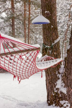 Hammock under the snow in the garden in winter. Summer and vacation memories