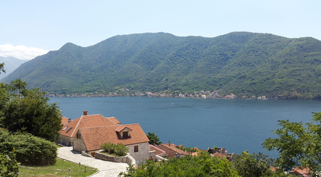 orange roofs of Perast town and green mountains - bay of Kotor in Montenegro