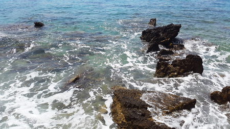 dark stones and green water with white foam - Adriatic sea