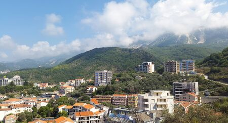 green landscape with houses under blue sky near Becici - resort of Montenegro Standard-Bild