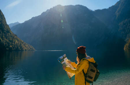 a girl in a yellow jacket and a red hat with a backpack in sunny weather looks at a map in the mountains near a blue turquoise lake side view