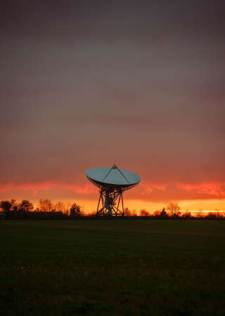 large satellite dish from the space station in the field on the horizon against the background of sunset