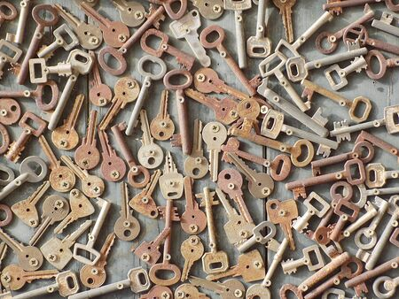 Wooden background with different old rusty keys bolted in chaotic order. Top view. Privacy or security concept.