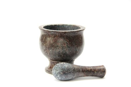 Stupa - a tool for crushing and grinding. Dark dishes on a white background