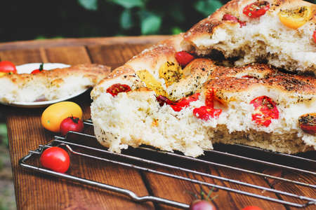 Focaccia. Italian bread. Bread with tomatoes. Homemade food. Cook at home. Fresh bread on the wire rack