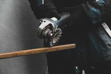 A man works with an angle grinder. Metal grinding process. Stripping rusty metal