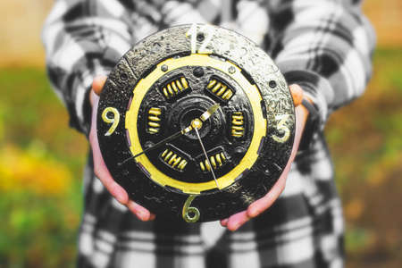 A clock from a car clutch disc. Black watch with gold elements. Man holding a clock in his hands