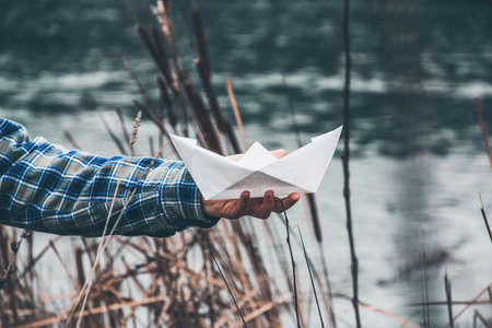 A man holds a paper boat in his hand, against the background of the river. Paper product Standard-Bild