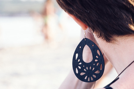 A closeup of a big black ornamented earing on a short hair-cut young brunette woman with her hand at her face Stock Photo