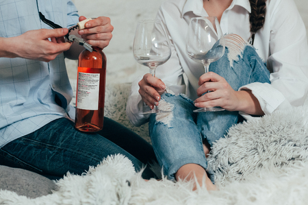 A young couple in blue jeans opens a bottle of rose wine on a bed with pillows