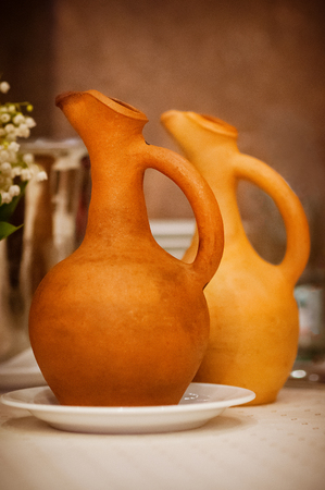 Soft focused wine jugs of terracotta color on the table, family restaurant, lunch time, simple style