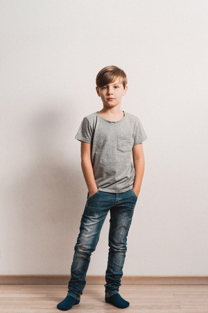 a cute boy stands next to white wall, grey t-shirt, blue jeans, hands in pockets 免版税图像